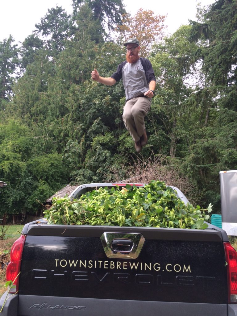 Brewmaster Cédric Dauchot jumps for joy as he tries to pack as many hops into his truck as possible.