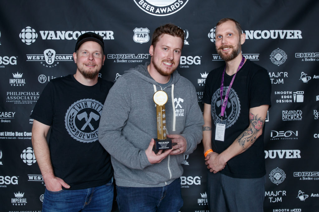 photo of three men with middle holding trophy for Best in Show awarded to Twin City Brewing at 2018 BC Beer Awards ceremony