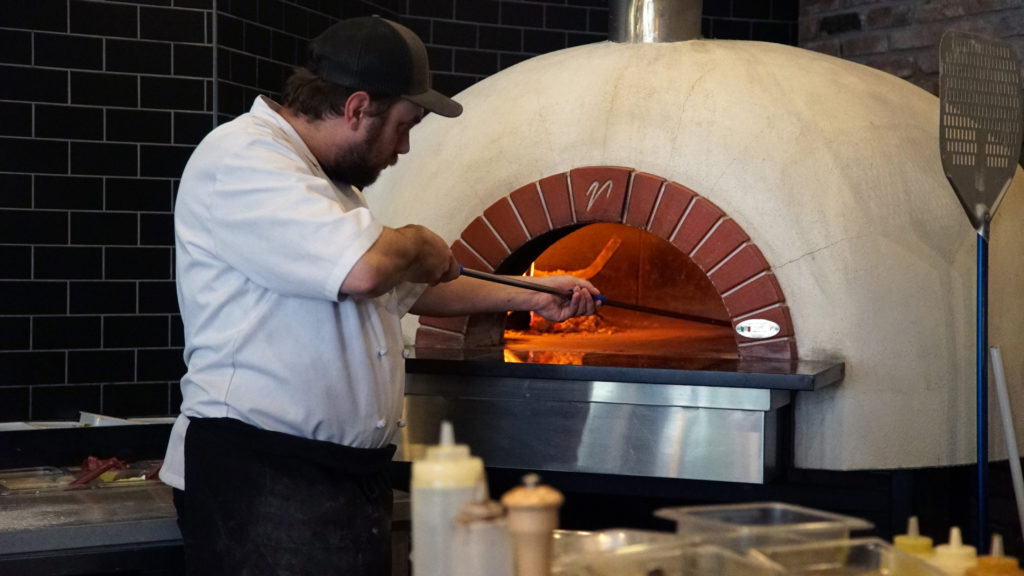 image of man putting pizza in wood-fired oven at CrossRoads Brewing in Prince George, BC