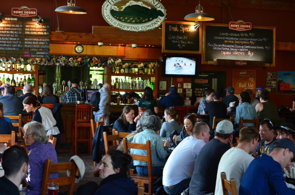 people enjoying beers at Howe Sound Brewing in Squamish