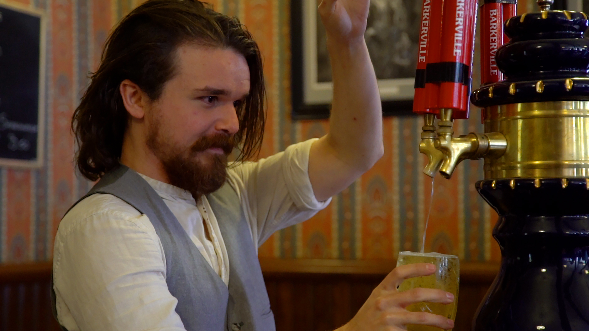 man in historic costume pours a pint of beer in gold rush town of Barkerville