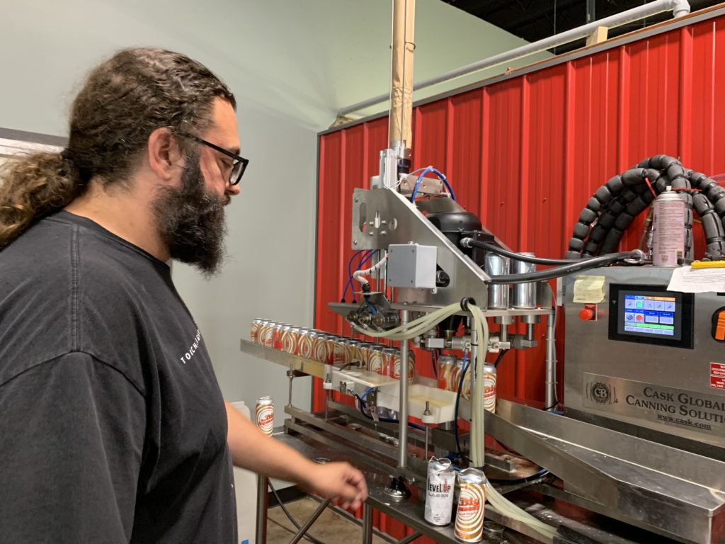 image of Craig Swendson, owner of Torchlight Brewing in Nelson, BC, operating packaging line