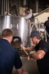 men taking spent grain out of barrel