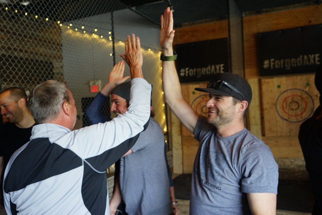 a few men high-fiving at Forged Axe Throwing in Whistler, BC