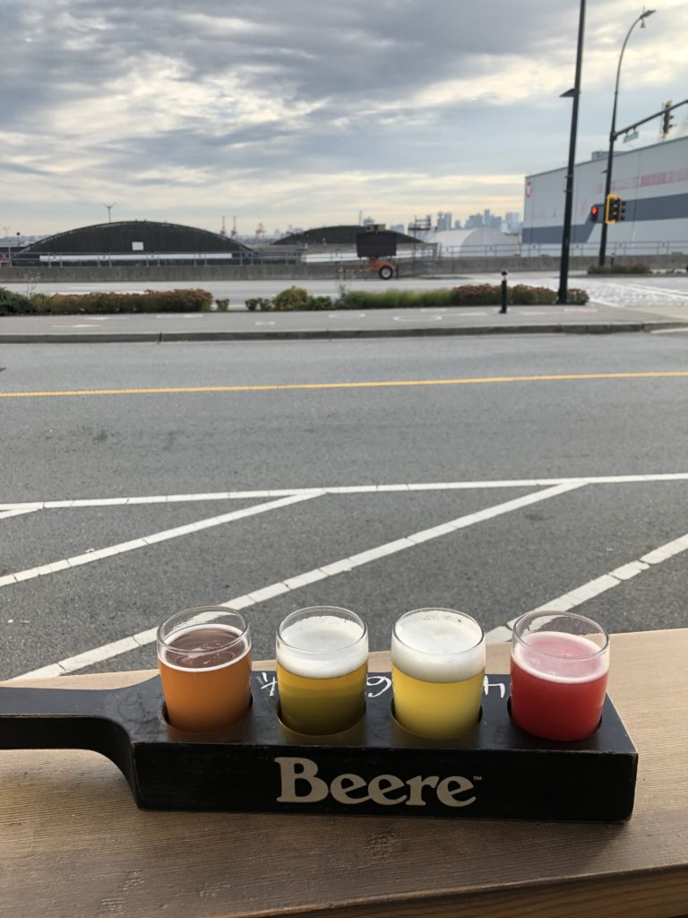 a flight of beer from Beere Brewing with a view of Vancouver's North Shore