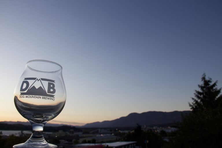 Dog Mountain Brewing glass with Port Alberni's dusk in background
