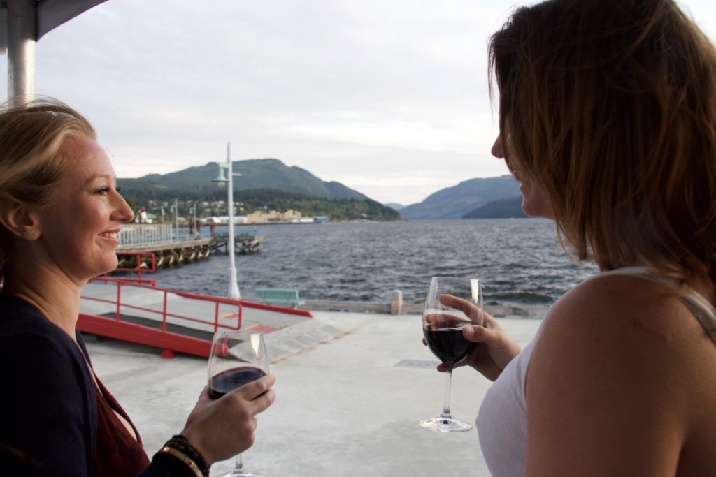 two women with beer glasses in hand looking out onto a dock at Swept Away Inn in Port Alberni