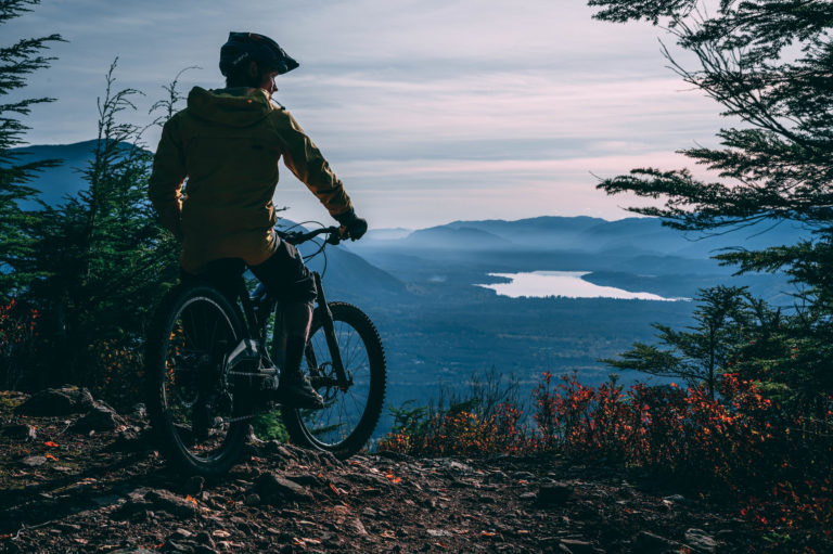 image of mountain biker Mark Matthews taking in the view of forests and water from top of Terrace Mountain in Northern BC