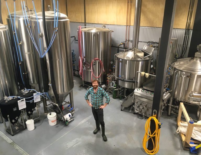 Smithers Brewing Company's co-owner and brewmaster, Cam McKeigan, standing among the tanks in the brewhouse.