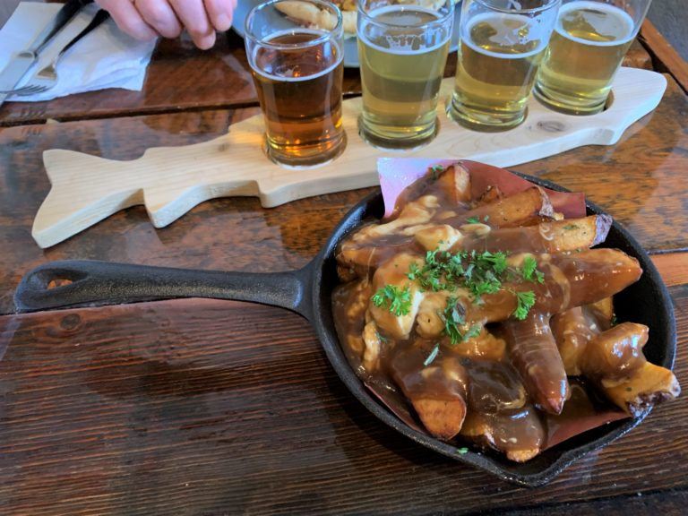image of Provisions Kitchen's hand cut Russet fries poutine in foreground, with beer flight from Kettle River in background