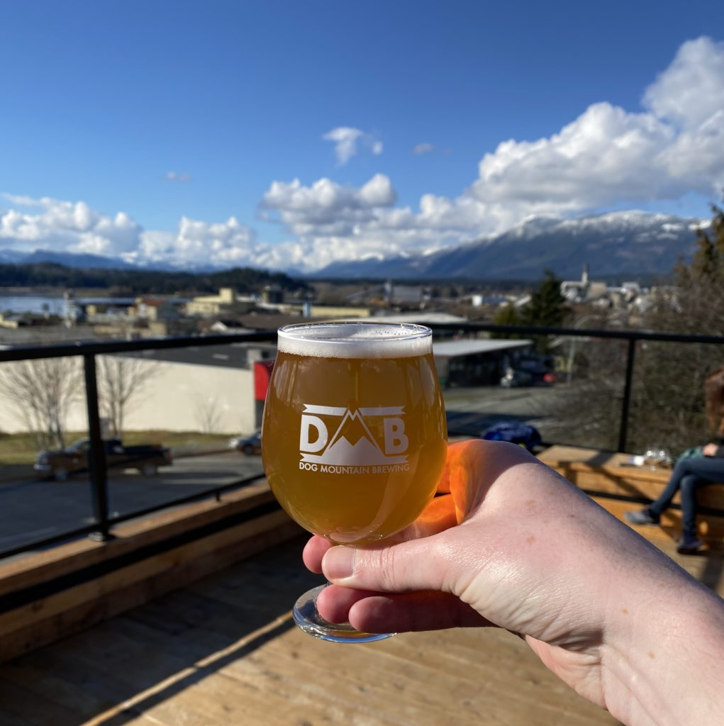 image of small glass full of beer on Dog Mountain Brewing's rooftop patio with Port Alberni in background and fluffy white clouds and snow-capped mountains contrasting blue sky