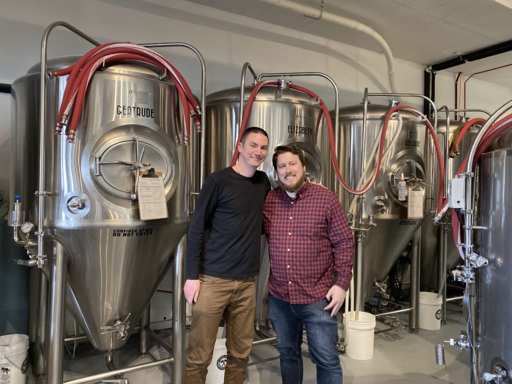 photo of Aaron Johnson, host of podcast with Aaron Colyn, owner of Twin City Brewing in Port Alberni standing in front of brewtanks
