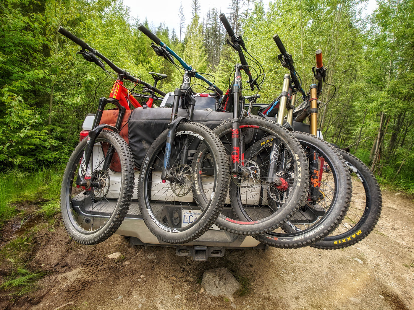 Mountain bikes loaded in the back of a truck on a forest service road.