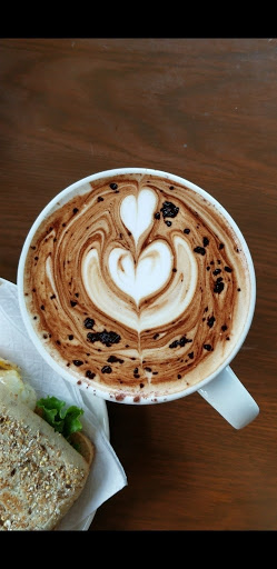 Photo of a coffee cup with coffee art in the foam, next to a sandwich in the lower left corner.