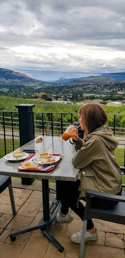 Photo of a woman sitting at a table with a food tray on it, overlooking the Okanagan Valley as she sips on a drink.