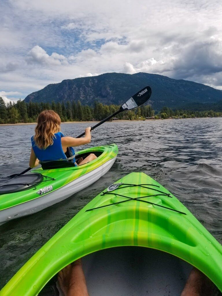 Photo of front of a kayak on Little Shuswap Lake, with a woman in another kayak to the left paddling.